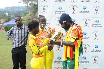 Jamaican Reggae star Riley (R) admires trophies presented to her by the Lady Cricket Cranes skipper Kevin Awino (L) and Janet Mbabazi (C)